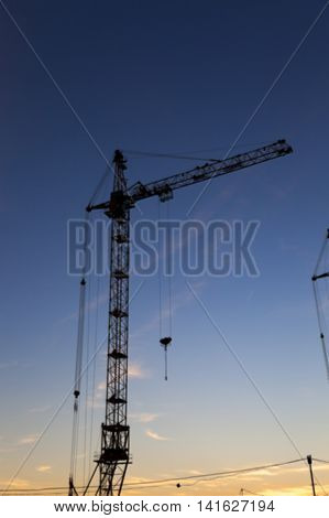photographed close-up construction cranes during construction of a new multi-storey residential building, defocus