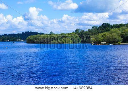 People rowing canoe paddling in calm blue Loch Lomond lake in Scotland, 21 July 2016