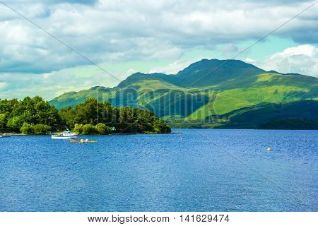 Canoe on calm blue Loch Lomond lake in Luss in Scotland UK, 21 July 2016