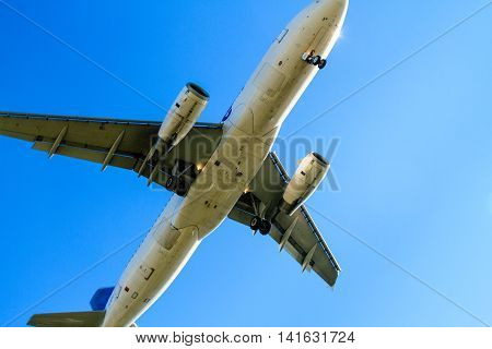 Airplane Flying In Blue Sky While Landing