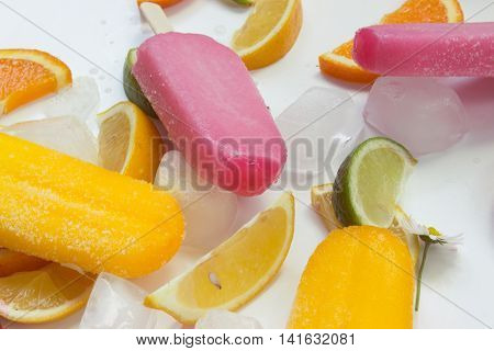Pink and yellow ice creams with ice and fruits on the table