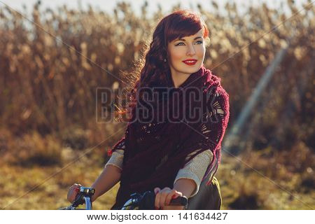 Beautiful young woman in long skirt and wool scarf riding bicycle in field. Outside shot. Autumn season. Copy space.