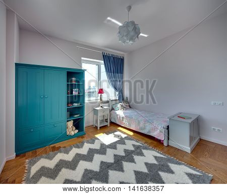 Kid's bedroom with light walls and a parquet with carpet on the floor. There is a bed with colorful veil and pillows and a toy, turquoise bookcase with toys and books, nightstand with a lamp, commode.