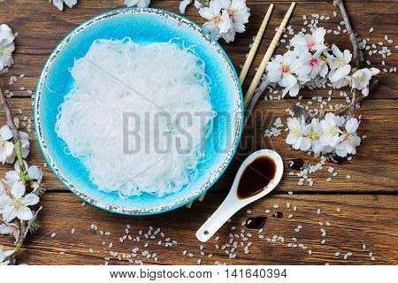 Asian food. Bowl of rice flat noodles, cherry tree branches with white flowers, soya and japanese rice on wooden background. Top wiew