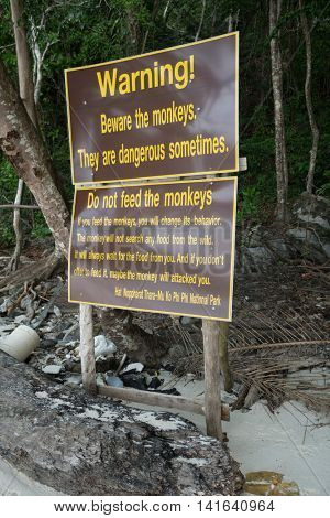 Beware of monkeys warning sign and others on a tropical beach