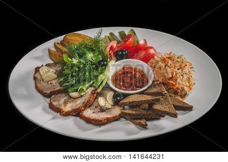 Meat delicacies, black bread and spices pickled cucumbers, tomatoes, sauerkraut,    on white plate isolated on black background