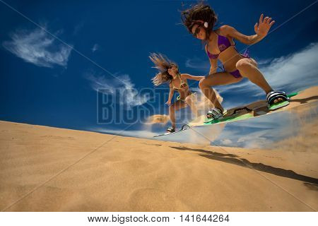 Kitesurf girls jumping on sandy beach with their arms raised against blue sky