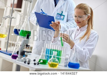 smiling female scientist using chemistry liquid for research in laboratory