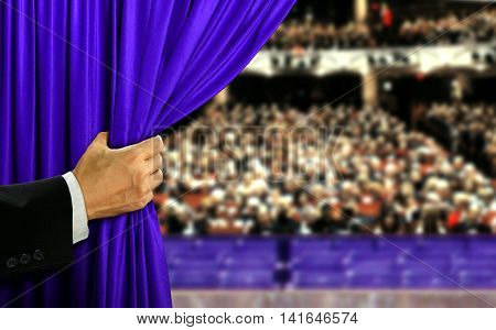 Hand opening blue stage curtain and audiance