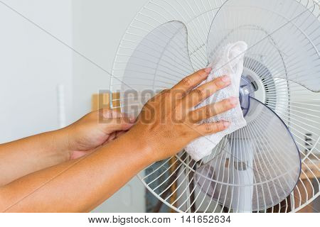 Close up horizontal photo of male hand cleaning dirty electric fan blade with cloth.