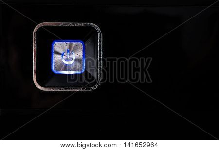 Old rusty power button with blue light on black metallic background