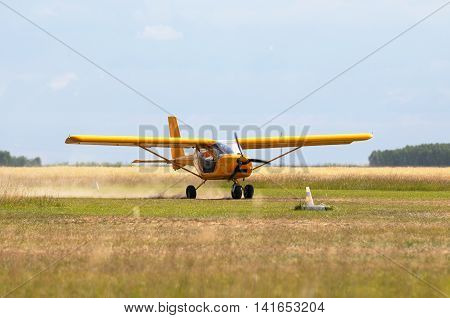 Private propeller-driven airplane landing on green grass