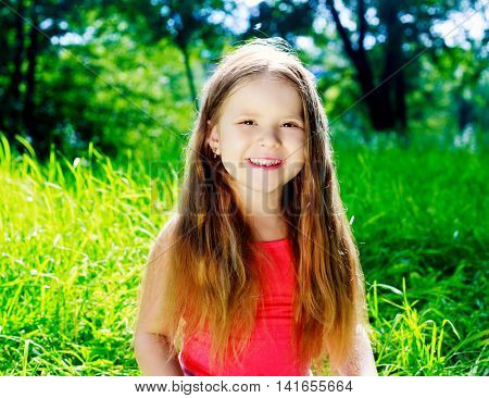 happy girl with long hair in the park on a summer day