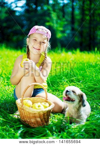 happy girl with a dog having a picnic on a summer day