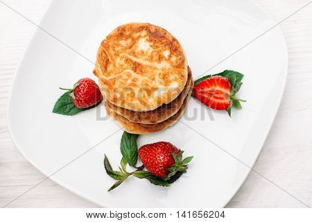 Plate of pancakes with strawberry flat lay, copyspace. Top view on sweet flapjack dessert with fresh berries