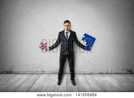 Businessman stands holding pieces of puzzle with EU and UK flags on them. Brexit puzzle concept. British withdrawal. Significant decision. Substantial choice. Europe and United Kingdom.