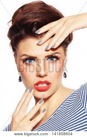 Portrait of young beautiful sexy woman with stylish pin-up make-up and striped manicure over white background