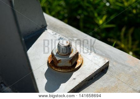 Rusty screw metal nut with bolts on steel beam background