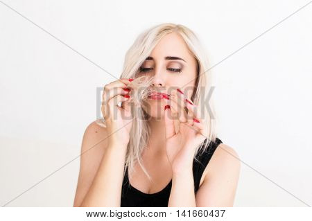 Blonde woman looking at her hair tips. Bad condition of dyed hair, awful hairdresser work