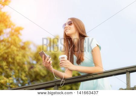 Beautiful young brunette woman listening music in headphones, holding a cup of coffee and enjoying music. Photography from low angle