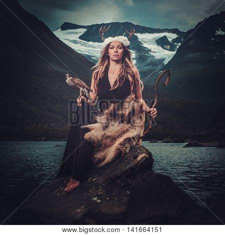 Nordic goddess in ritual garment with hawk near wild mountain lake in Innerdalen valley, Norway.