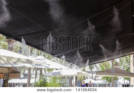 Granada, Spain - August 5, 2016: Awning sprinklers splashing vaporized water at terrace bar in order to cool the hot summer temperature in Spain