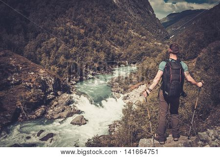 Man hiker with backpack standing on the edge of the cliff with epic wild mountain river view. Norwau.