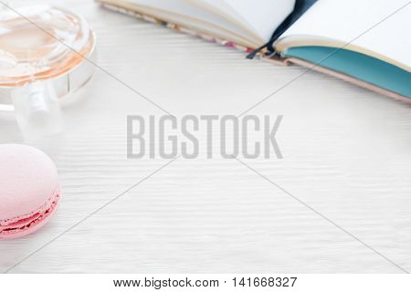 White wooden background with female accessories, free space. Copy space on table with notebook, macaroon and perfume. Young romantic girl workplace