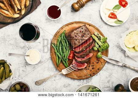 Rare steak with side dish of French beans and glass of red wine on a wooden board top view