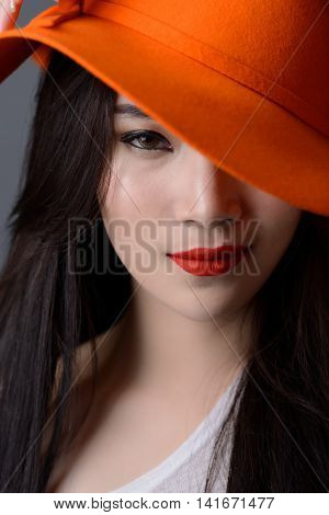 portrait close up of beautiful asian woman model in orange striped hat with red lips