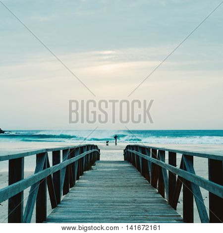 a wooden boardwalk leading to the sand of a beach and the silhouette of a dog and a young caucasian man in the distance taking a picture in front of the sea at sunset
