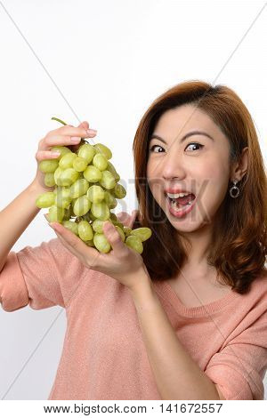 Beautiful asian woman shocked expression while holding green grape