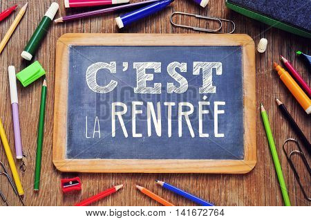 high-angle of a chalkboard with the text cest la rentree, back to school written in french, on a rustic wooden table full of markers and pencil crayons of different colors