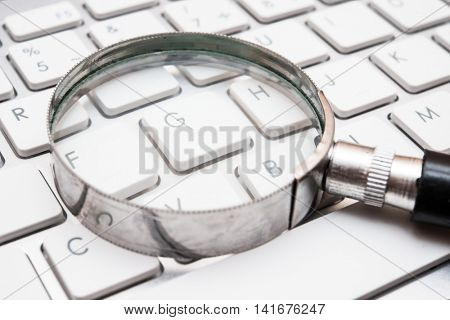 Hand lens on a keyboard, internet search concept