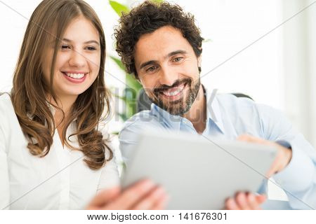 Young smiling couple using a digital tablet