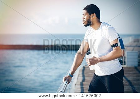 Pensive african young sportsman listening to music and drinking water on pier