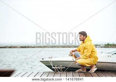 Young handsome sailor in yellow cloak holding rope at the pier and looking away
