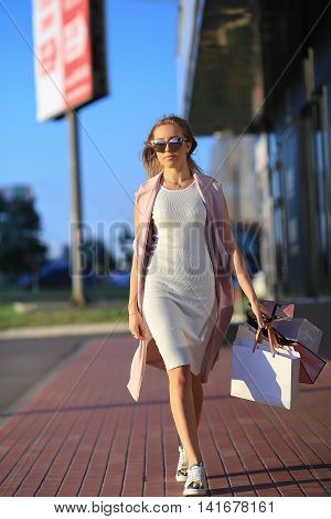 girl walking with shopping bags. Concept of woman shopping.Shopper. Sales.