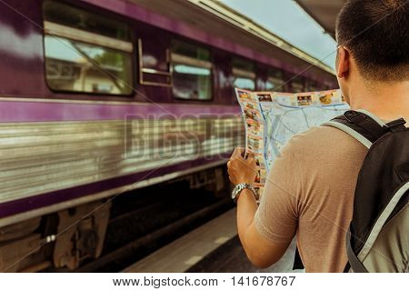 Young man traveler with backpack look searching location map at the train station Travel concept soft focus vintage tone