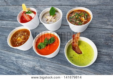 Variety of restaurant hot dishes, healthy food. Japanese miso soup, asian fish soup, russian borscht, english pea soup with bacon, mushroom soup, spanish gazpacho at blue rustic wood
