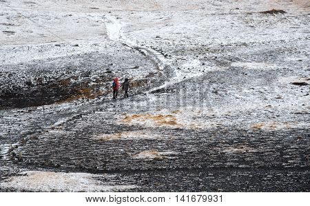 Unrecognized people trekking on a curved nature trail covered in snow in Iceland