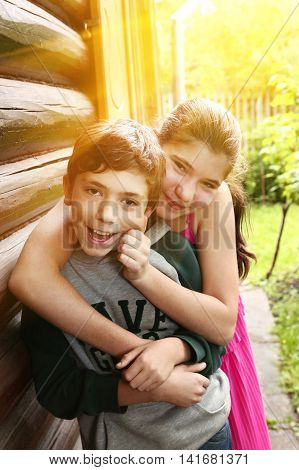 teenager siblings brother and sister hug close up portrait on the summer cottage house and garden sunny background