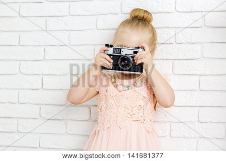 Little girl with retro camera in hand closeup