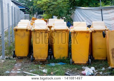 Row of large yellow wheelie bins for rubbish