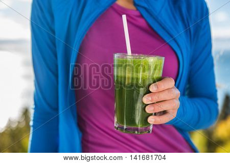 Healthy lifestyle clean eating person holding glass of fresh blended spinach leafy greens drinking smoothie as part of a health diet for a fitness active life. Morning breakfast closeup outdoor.