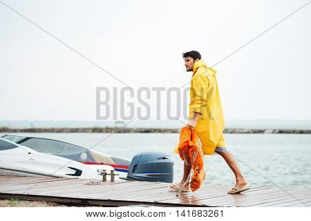 Side view of a young handsome sailor man in yellow cloak walking at the sea pier holding life vest