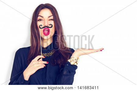 Surprised winking model Girl holding funny mustache on stick and showing empty copy space on open hand palm for text, white background. Girl presenting point. Proposing product. Advertisement gesture