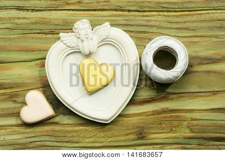 White angel photo frame with white bobbin of thread and decorative heart