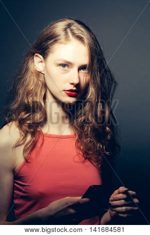 Young girl with pretty serious face brown curly hair fashion makeup in red sexy top holding mobile in hand on dark background studio