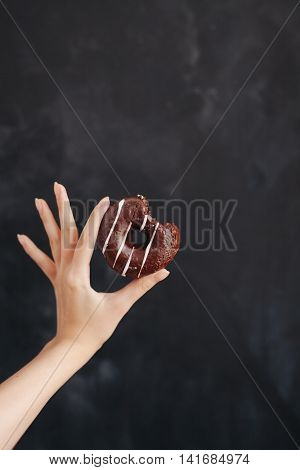 Chocolate strip donut in a woman's hand